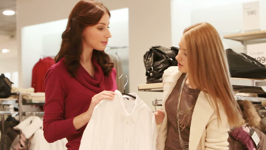 Two girls picking a white shirt in the shopping mall