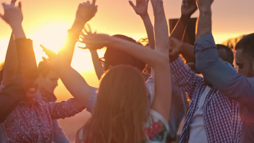 Group of young multi-ethnic people dancing with raised arms to the music played by dj at rooftop party at sunset #19079311