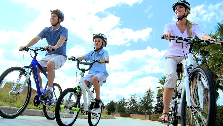 Healthy young caucasian family outdoors together riding their bicycles