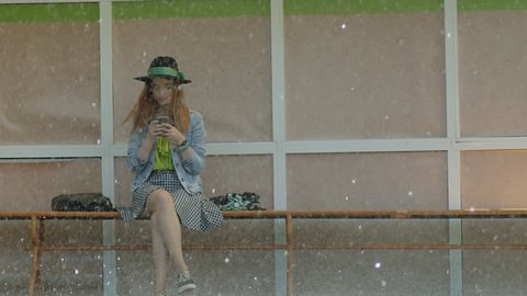 Girl sitting at the bus stop in the rain and texting with mobile phone . People running in the rain with umbrellas. Shot on RED EPIC Cinema Camera in slow motion.