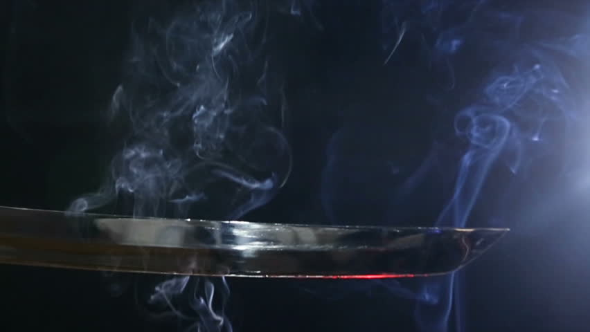 Japanese katana sword. Blade close-up on a dark background with blue light filter with incense smoke. Steel tempering