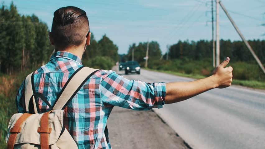 Back side of boy with backpack hitchhiking at road in summer sunny day. Cars. Countryside.