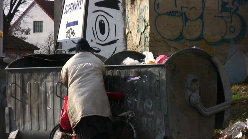 ZRENJANIN, SERBIA -  JANUARY 2012 - Hungry person collects food from rubbish bins circa January 2012 in Zrenjanin, Serbia.