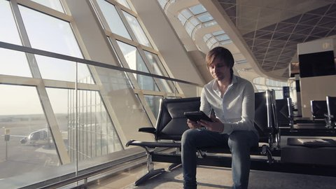 handsome smiling man holding tablet and working at the airport, technology, travel and modern life concept