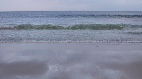 The waters of the Atlantic Ocean wash gently onto a sandy beach on Cape Cod, Massachusetts. This scenic part of New England is a popular vacation destination during summer months.