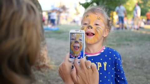 SOFIA, BULGARIA - AUG 27, 2016: Painting body art on face of little cute child girl - mom takes smart phone photo picture for social media
