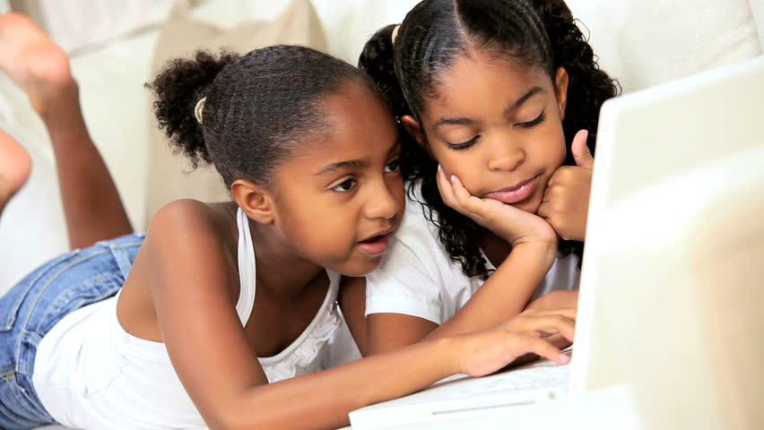 Cute little african american girls lying on their home sofa playing internet games on a laptop