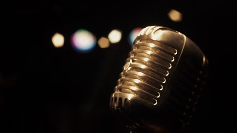 Concert vintage glare microphone on stage in empty retro club. Spotlights. Close up.