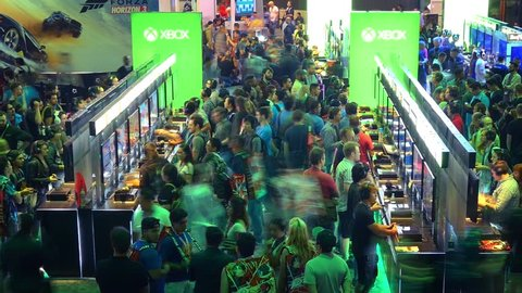 LOS ANGELES - June 16, 2016: Pan across crowds of gamers playing games in Microsoft XBOX booth at E3 2016 expo in Convention Center. E3 is an annual trade fair for the video game industry. Timelapse.