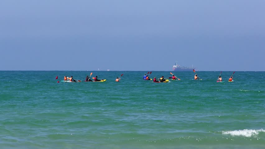 People having fun paddling their canoe and kayak in a blue sea. A huge cargo ship in the background | Shutterstock HD Video #19256767