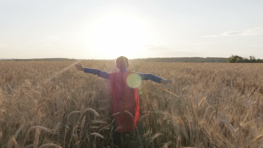 Boy with a superman cape stands in a golden fields looking to the horizon