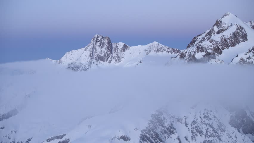 Slow Mo Aerial shot of snow peaks with clouds below at dusk in Courmayeur, Aosta Valley/Italy (Courmayeur, Aosta Valley/Italy - March, 2016)