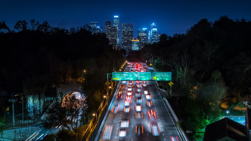 Beautiful view of Los Angeles Skyline from 110 Freeway at dusk. Close up. Traffic passing by. Timelapse. California, United States. | Shutterstock HD Video #19272145
