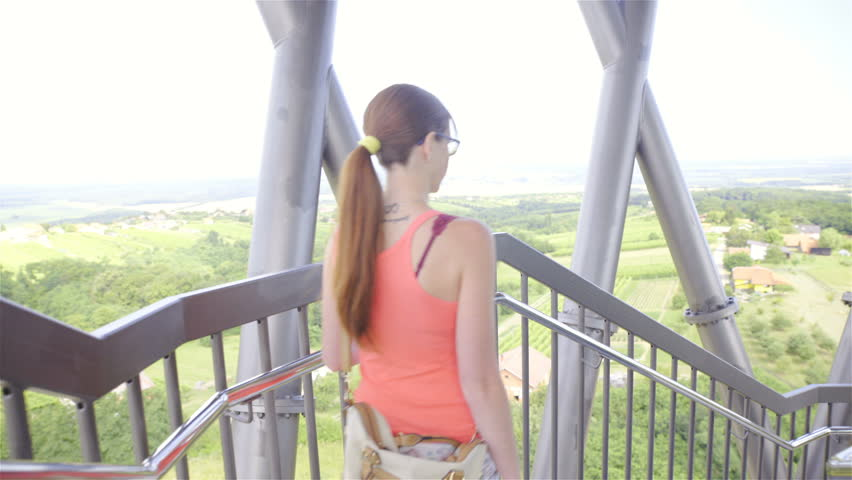 Woman walk downstairs of tall Vinarium tower 4K. Camera on gimbal stabilizer walk behind attractive female person walk down the stairs of iron tower with beautiful view on landscape around. | Shutterstock HD Video #19314181