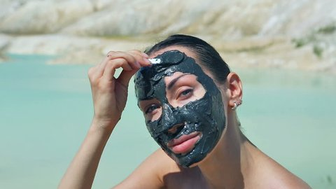 Woman with Black Clay Facial Mask. Beauty, Wellness. Spa Outdoor, Beautiful Young Woman with natural Dead Sea mud Facial Mask on her Face near the Lake with Black Cosmetic Healing Clay