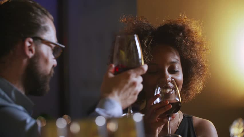 Young Couple Toasting Wine Glass In Luxury bar. Dating. Hipster and black woman on romantic dinner drinking at bar | Shutterstock HD Video #19360684