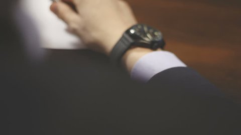Businessman checking wrist watch. The watch on the hand. The man in the jacket looks at his watch. Businessman sitting at a desk for hours. Business meeting. Attributes businessman. Men's Accessories