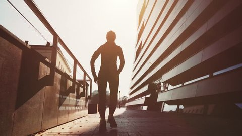 Runner Woman Running in the Sunny Modern Morning City. Steadicam STABILIZED shot, SLOW MOTION 120 fps. Athletic Fitness Sportswoman Listening to Music during Training. Healthy Lifestyle. Lens Flare.