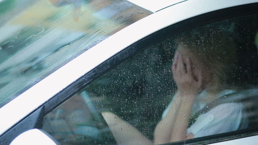 Sad girl crying in the car. rain on the street. woman in hysterics | Shutterstock HD Video #19395103