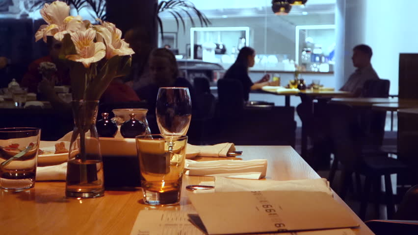 Interior of the restaurant decorated table in the foreground on the background of silhouettes of people at dinner flowers glasses menu napkin