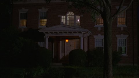 night tilt up left upstairs windows Raked right eastern two story all red brick colonial house, white trim, dormers, portico, green bushes trees