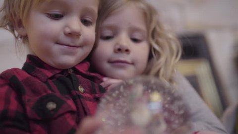 Brother And Sister Curl Up Together And Watch The Snow Settle In A Snow Globe