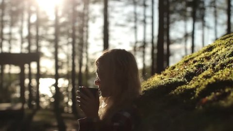 Silhouette of a Girl With a Mug of Tea in the Sunset at the House With a Roof of Moss