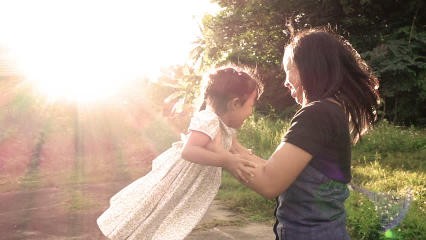 Slow motion of mother and daughter spinning around in flare sunset. Concept of happy family desire in no noisy home and carefree in day time