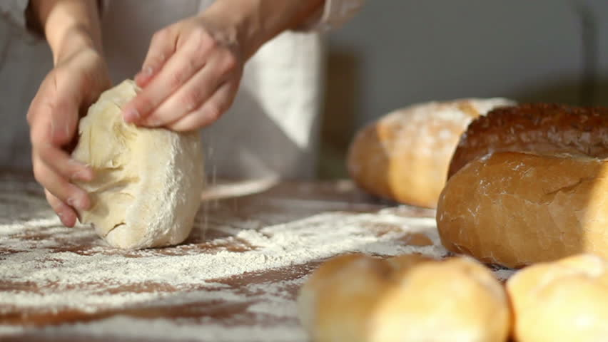 Baker kneading dough in flour on table, slow motion, dolly shot
