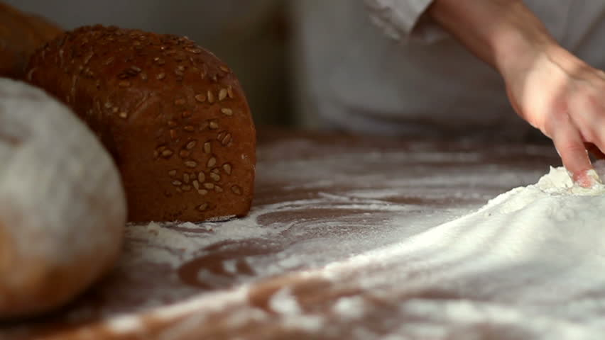 Baker mixing egg with flour on table, slow motion, dolly shot