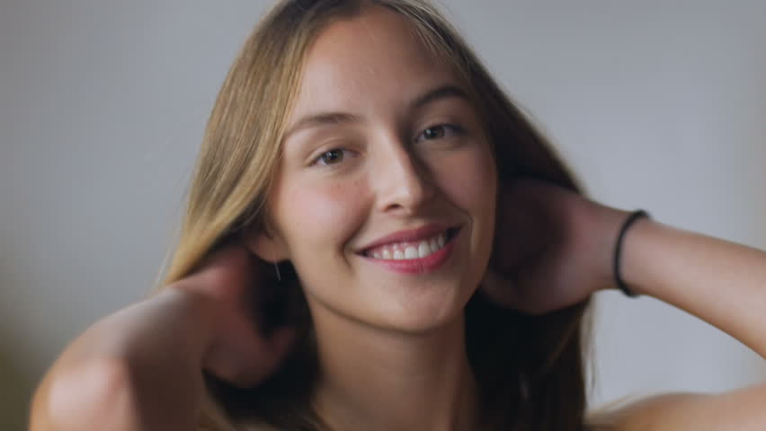 An attractive young smiling blond woman plays with her healthy hair in slow motion against a white backdrop | Shutterstock HD Video #19530721