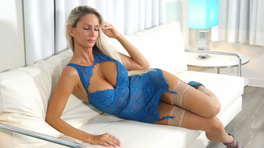 e020bc68540 Sexy blond lingerie woman in blue lace on couch wearing nylon stockings
