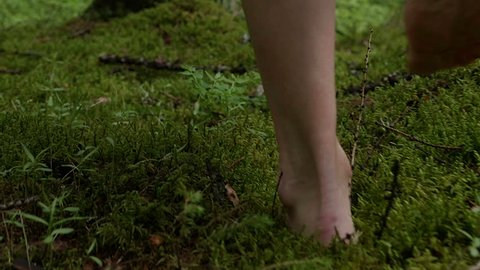 girl walks barefoot in the woods in a cloak