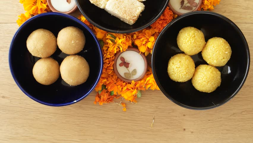 Tilt up close up across Indian sweets, flowers, diyas on a wooden background for Hindu festival of lights, Dusshera and Diwali preparation and celebration ingredients