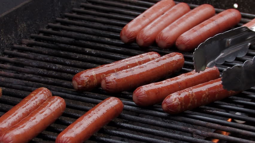 Grilling hot dogs on a barbecue