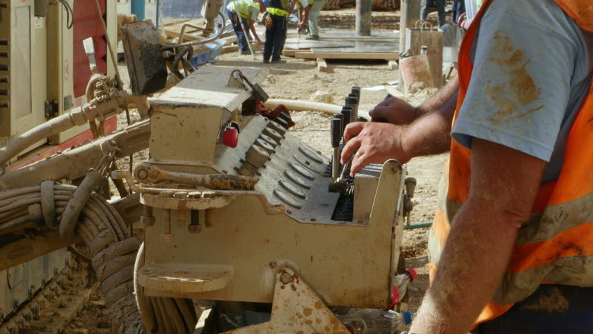 Worker hands on control panel operating drilling machinery at construction site.