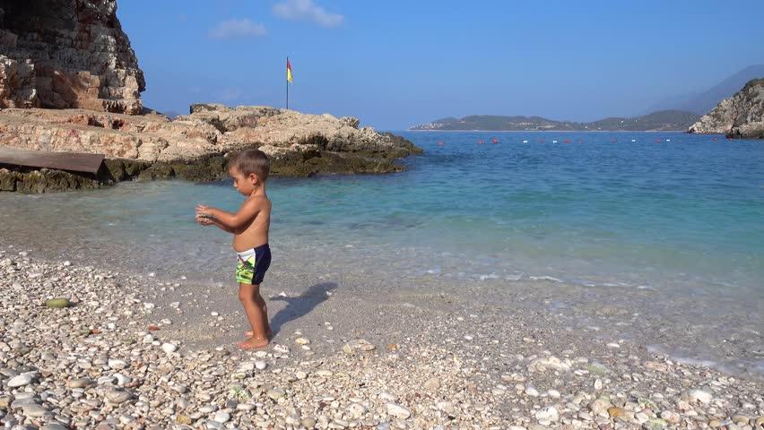 4K Boy plays in swash on empty beach  #19620361