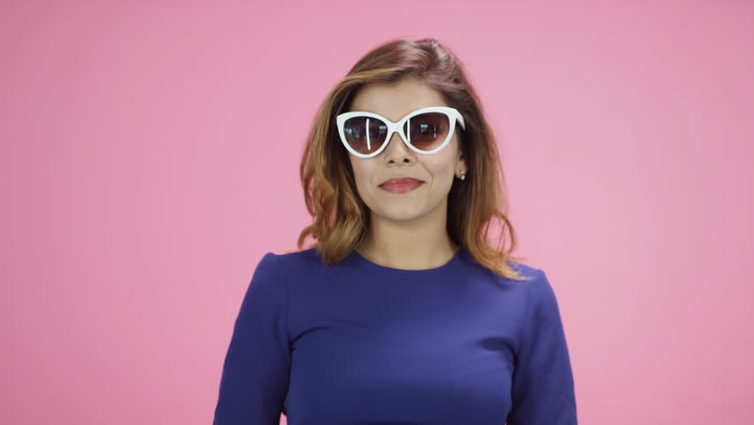 Young Asian woman looking into camera on pink background wearing sunglasses #19660321