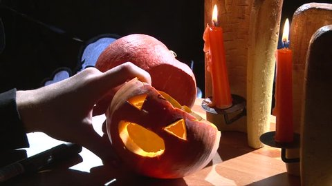 Put vampire fangs teeth in Halloween pumpkin mouth, table with candles
