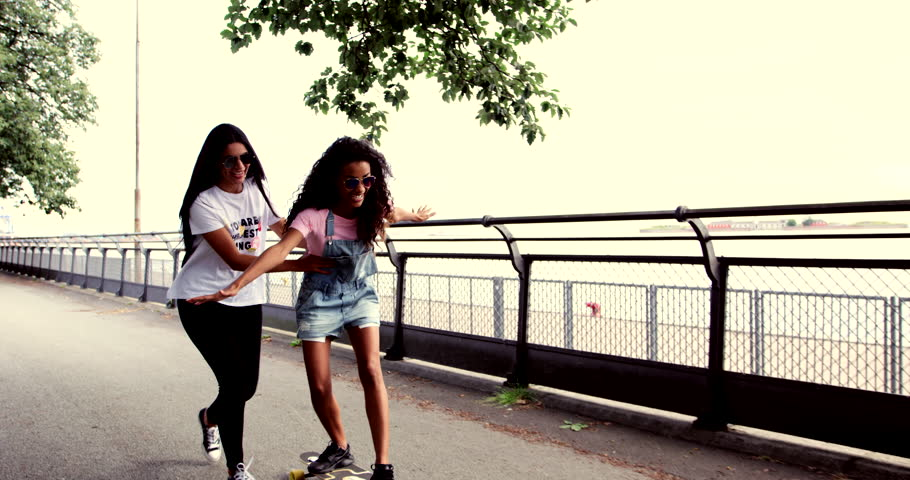 Laughing young woman in sunglasses being taught skateboarding by a friend who is supporting her around the waist as they walk along a promenade