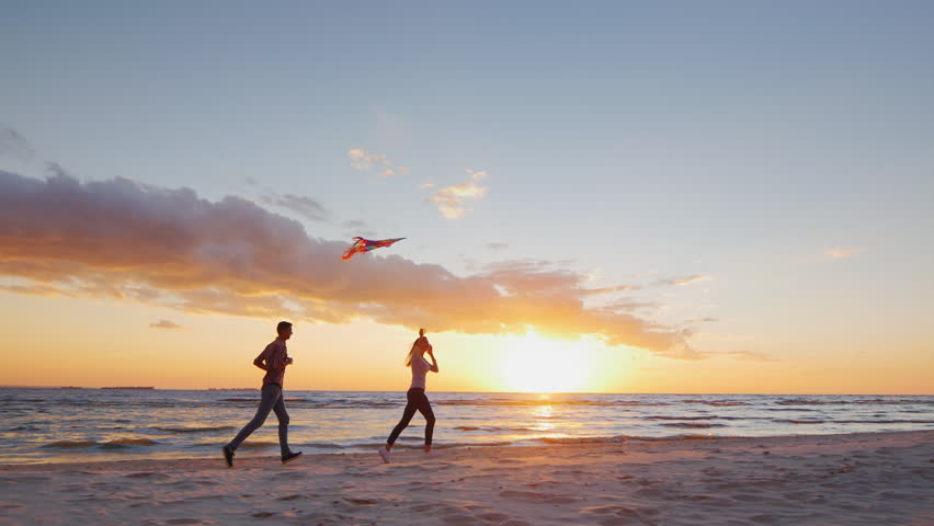 Young couple playing with a kite on the beach at sunset. Steradicam slow motion shot #19687261
