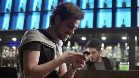 4K Young man sitting at a bar and sending message on the mobile phone with smile. Shot on RED EPIC Cinema Camera.