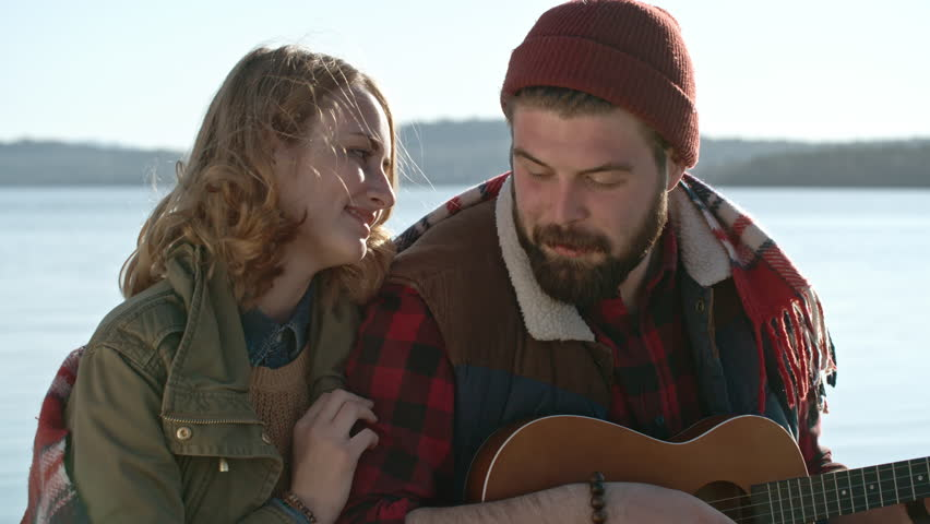 16fd71fd1cd Medium shot of young man with beard wearing beanie hat sitting with his  girlfriend near lake playing on mini-acoustic guitar and singing to his  blond ...