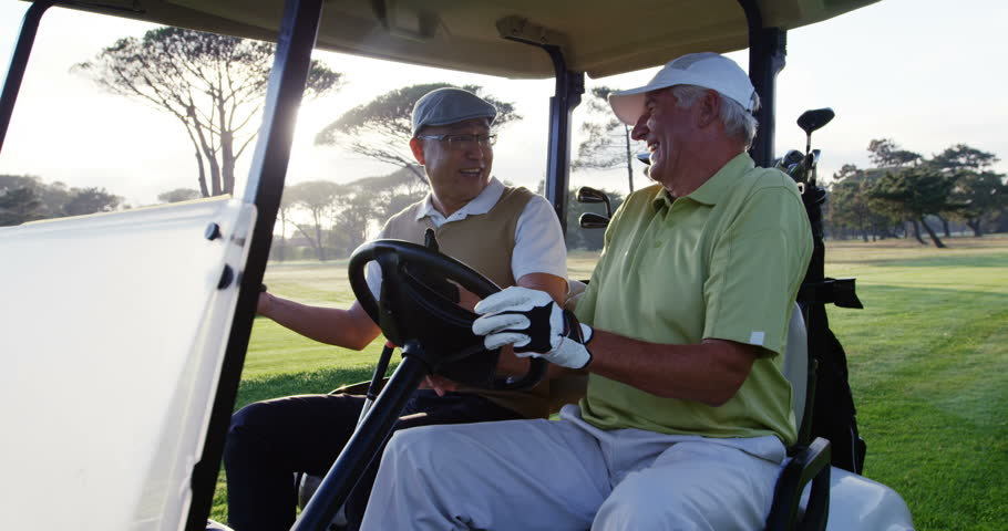 Two golfers laughing together in their golf buggy at golf course