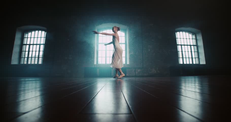 Beautiful ballerina in white dress performs pirouettes in the Studio, slow motion