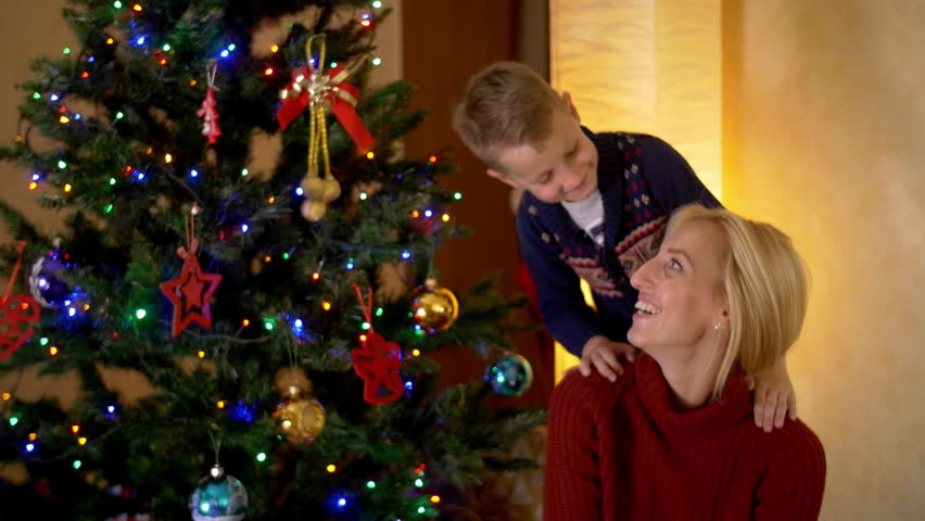 Happy blond mother with her son under a christmas tree. | Shutterstock HD Video #19736401