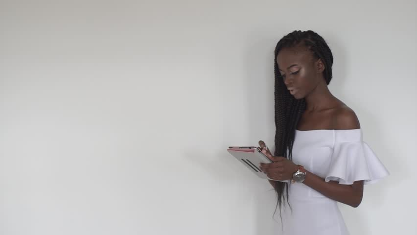 3e87c393c34e Close up portrait of a beautiful african female fashion model typing  something on tablet on blank white background