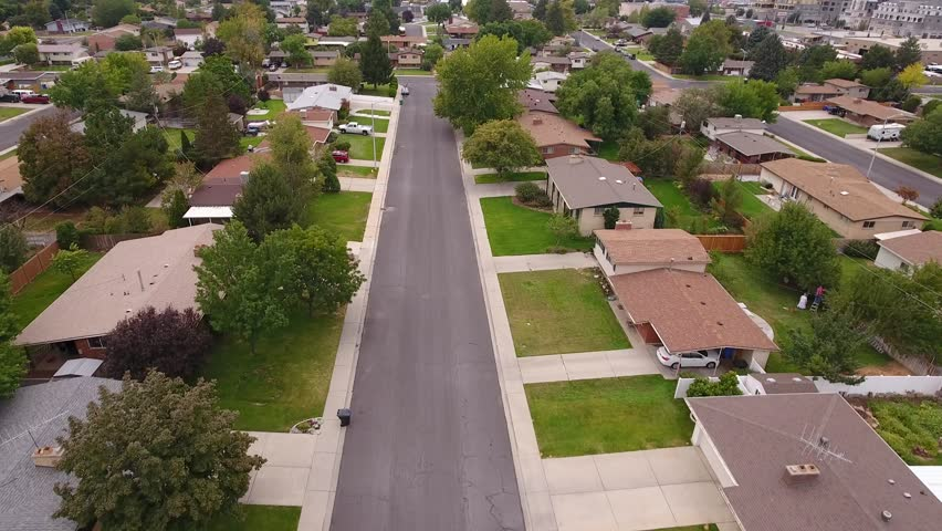 An aerial shot of cars driving on the roads in the busy city suburb neighborhoods