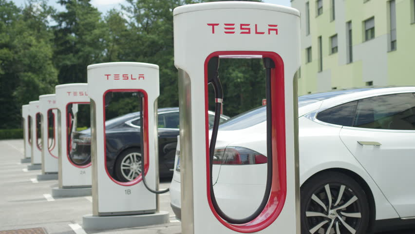 LJUBLJANA, SLOVENIA - JULY 10 2016: White and black Tesla autonomous electric cars refilling energy at free of charge super fast charging station on parking lot. Luxury vehicles charging battery