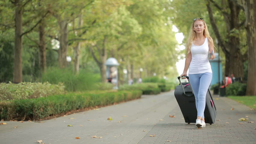 woman walking with luggage in hands, talking on smartphone #19832941